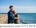 Young couple standing outdoors on beach, talking. Copy space. 57717676