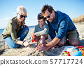 Young family with small boy sitting outdoors on beach, playing. 57717724