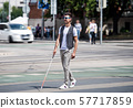 Young blind man with white cane walking across the street in city. 57717859