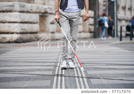 Midsection of young blind man with white cane walking across the street in city. 57717870
