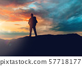 traveller standing on edge of hill over sunset 57718177