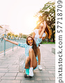 Two stylish excited girls have fun and skateboard 57718709