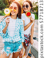Two young stylish girls walk around the Sunny city 57718713