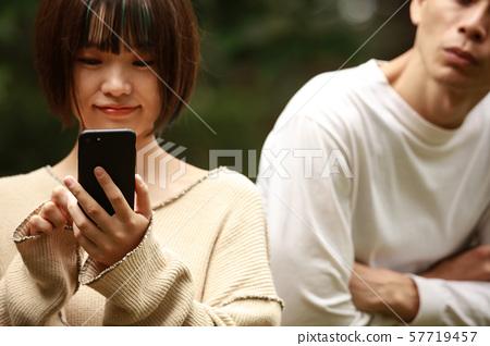 一個男人偷看女人的智能手機 57719457