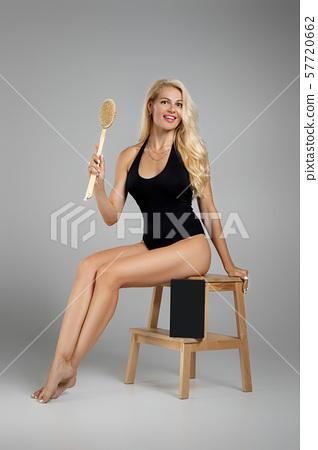 beautiful woman making a scrub massage with big brush. 57720662