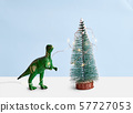Funny green Tyrannosaur Rex with lights decorating pine tree. Minimal 57727053