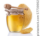 Glass jar full of honey and wooden stick on a white background. 57730002