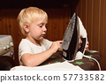 Little blond boy touches electric iron with his 57733582