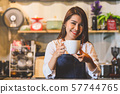 Asian female barista making cup of coffee. Young 57744765