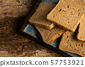 Brown bread slices on a wooden table 57753921