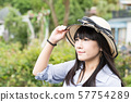 A Japanese woman in a hat travels in the mountains. 57754289