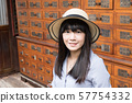 A Japanese woman in a traditional retro pharmacy in China. 57754332