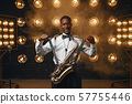 Smiling jazz performer with saxophone on stage 57755446
