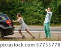Man and woman pushing broken car on road 57755778