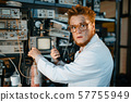 Strange engineer holds electric tube in laboratory 57755949