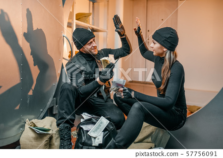 Two robbers in black uniform stuff bags with money 57756091