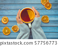 Hot warming tea with orange in female woman hand on blue wooden table 57756773
