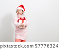 Girl holding a gift box in sweater and santa hat 57776324