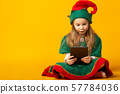 elf sits on the floor checking the list and making sure that they have all the presents 57784036