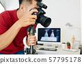 Photographer working in small studio 57795178