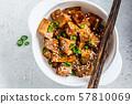 Fried tofu in teriyaki sauce in white bowl 57810069