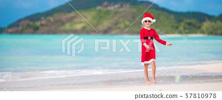 Adorable little girl in Santa hat on tropical beach 57810978