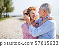 Senior couple on a holiday on a walk by the lake, hugging. 57815933