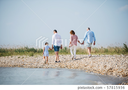 Rear view of multigeneration family on a holiday on walk by the lake, running. 57815936