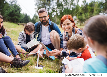 Group of school children with teacher and windmill model on field trip in nature. 57816210