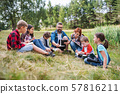 Group of school children with teacher and windmill model on field trip in nature. 57816211