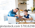 Mature father with small son sitting at table indoors, working on school project. 57816298