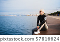 Portrait of young sportswoman sitting outdoors on beach. Copy space. 57816624