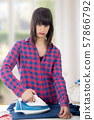 unhappy young beautiful woman ironing clothes 57866792