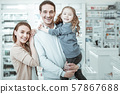 A cheerful family laughing and hugging near drugstore checkout 57867688