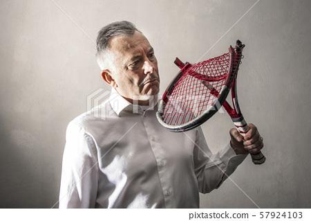 discouraged man watching his broken tennis racket 57924103