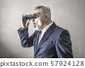 Businessman looking with a binoculars 57924128