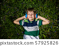 Smiling boy with arms under head lay under the sun 57925826