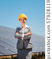 Woman investor in clean energy standing in front of solar panels 57928119