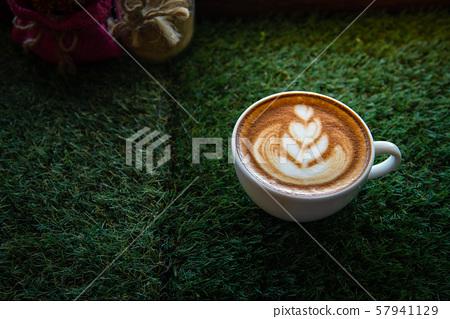 Hot art Latte Coffee in a cup on wooden table and Coffee shop blur background 57941129