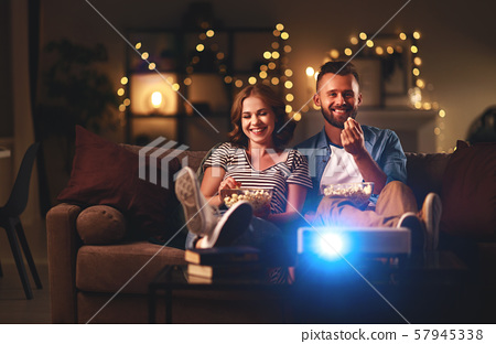 Family couple watching television at home on sofa 57945338
