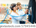Two women in a dry-cleaning company ironing 57945446