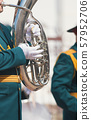 A wind instrument parade - a man in green costume playing tuba 57952706