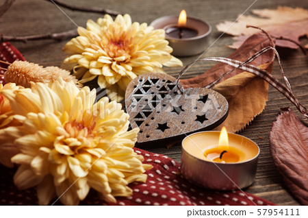 autumnal leaves and lit candles 57954111