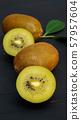 Golden kiwi on a black wooden table. 57957604