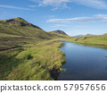 Beautiful green hills, lush grass and blue river next to camping site on Alftavatn lake. Summer 57957656
