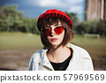Young woman in red beret and red glasses 57969569