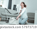 Curly red-haired woman feeling awful while using vacuum cleaner 57973719