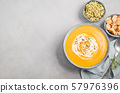 Pumpkin soup with cream, croutons, pumpkin seeds and thyme on a gray concrete or stone background Top view Flat lay Copy space 57976396