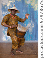 Handsome african drummer weared in traditional costume playing on djembe drum 57978675