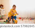 Cute lovely small baby girl learning to balance on her first bike at home. Toddler activity at 57982645